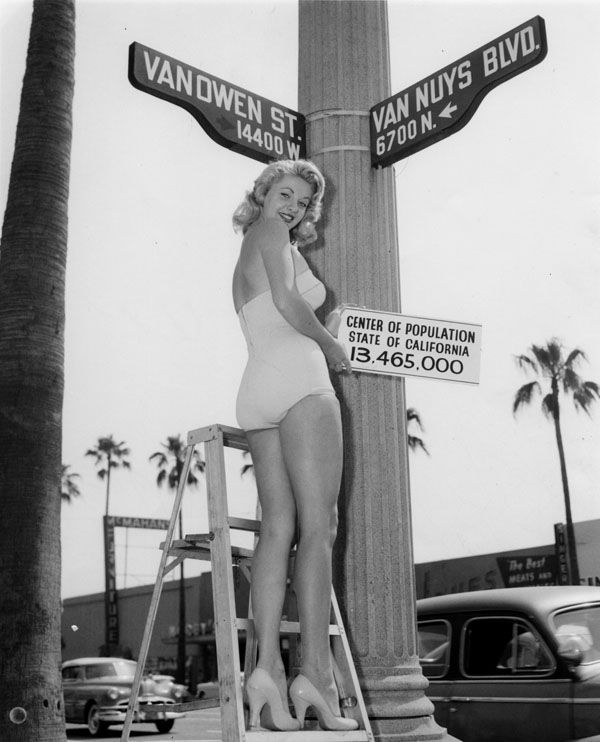 (1960)* - Miss Van Nuys on a step ladder holds up sign, reading: Center of population, State of California, 13,465,000, at the intersection of 14,400 W. block of Vanowen Street and 6,700 N. block of Van Nuys Blvd., Sept. 1960. Van Nuys Boulevard was renamed from North Sherman Way as the main boulevard in the town of Van Nuys, which got its name from longtime Valley wheat farmer Isaac Newton Van Nuys.