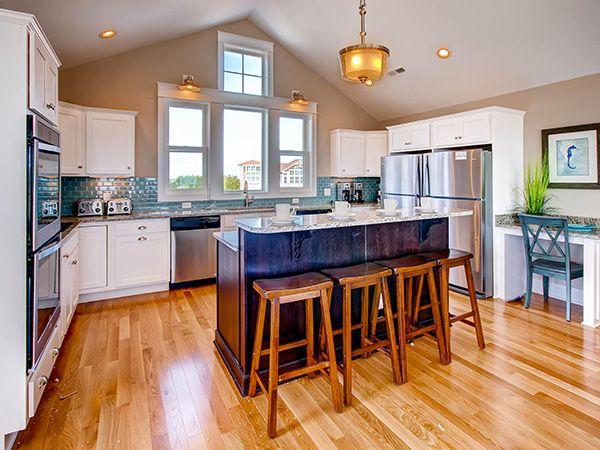 Time Out, 8 bedroom Ocean Front home in Salvo. Ascend to the top level to find the spacious great room with vaulted ceilings and astounding blue ocean views. Chefs in the family create culinary delights in the large open gourmet kitchen featuring granite countertops, custom cabinetry, two dishwashers, dual wall ovens and two full size refrigerators and a center island. The entire group can easily sit at the large dining table overlooking the Atlantic through the expansive wall of glass.