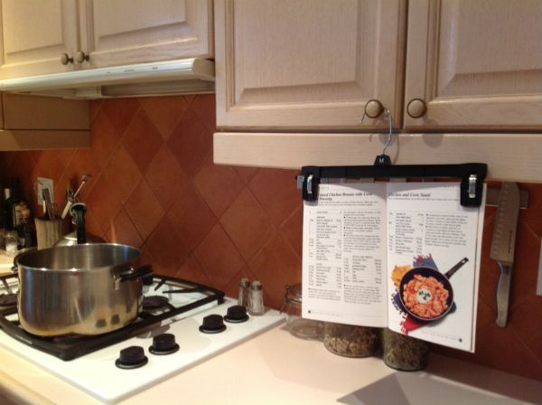 Keep recipes in clear view with a pant hanger | 12 Awesome Additional Uses For Everyday Objects