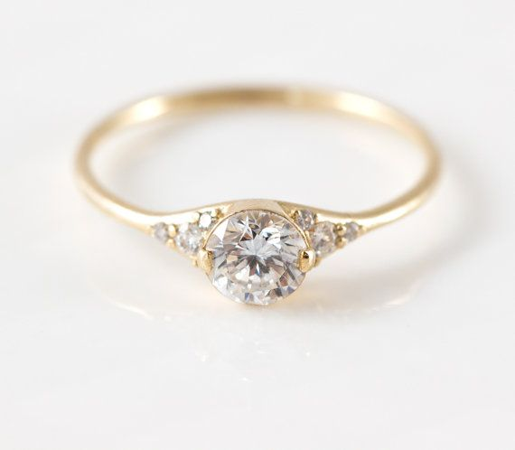 Featuring a stunning white center diamond surrounded by tiny white diamonds on either side, this antique-inspired engagement ring marries simplicity with sparkle in solid 14k yellow gold. A classic style to suit any era, this ring is designed to be a lasting treasure to cherish in your family for generations. ♦ Metal: Solid 14k yellow gold, bright polish finish ♦ Gemstones: White center diamond (5mm, I1 clarity D color, 0.48 carats), 8 side white diamonds (ranging in size from 1-2mm…
