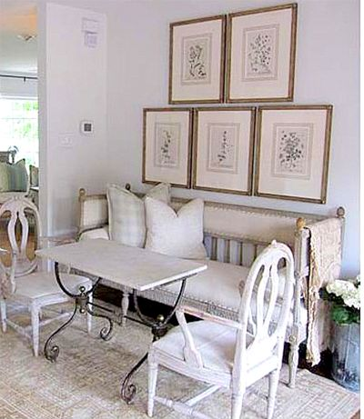 The Swedish Gustavian Settee | Maison and Co; love this seating area. Perfect for a chat and coffee and cardamom bread. Beautiful botanical prints on the wall above the seating area, iron table, great antique bench.