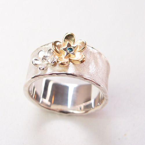 Handgemaakte ring met twee Vergeet mij nietjes. Eén in zilver en één in geelgoud die een kern heeft van blauwe diamant.