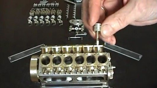 Patelo inserts a tiny piston into his miniature V12 engine. It's the worlds smallest functional V-12 engine. It runs on compressed air