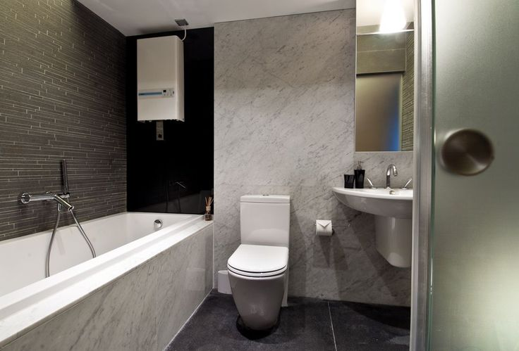 Fascinating White and Gray Bathroom Tile Design Idea with Gray Floor Tile, Whte Closet Seat, White Bathtub with White Bathtub Wall, and White Washstand