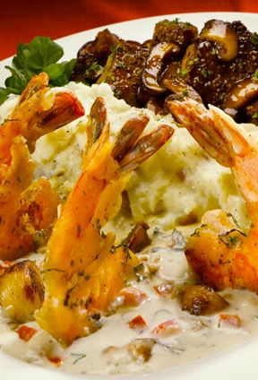 The Cheesecake Factory - Shrimp Scampi and Steak Diane - Our famous Shrimp Scampi sautéed with whole cloves of garlic, white wine, fresh basil and tomato. Served with medallions of Certified Angus Beef Steak covered with black peppercorns, a rich mushroom wine sauce, & mashed potatoes.