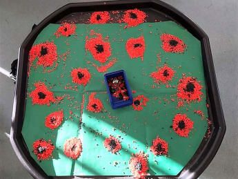 "For Early Years, Terri-Leigh had this idea for a Tuff tray for Remembrance Day. She said, ""After a successful rangoli pattern tuff tray we decided to colour some more rice to create some poppies. The children enjoyed it!"""