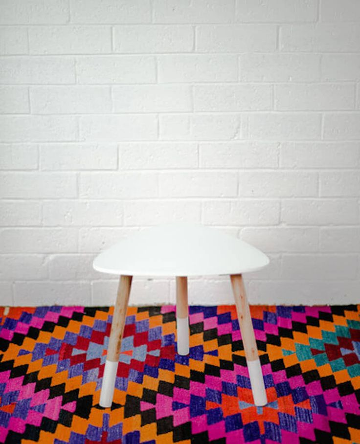 This handcrafted small side table comes in a fun triangular shape with paint dipped timber legs