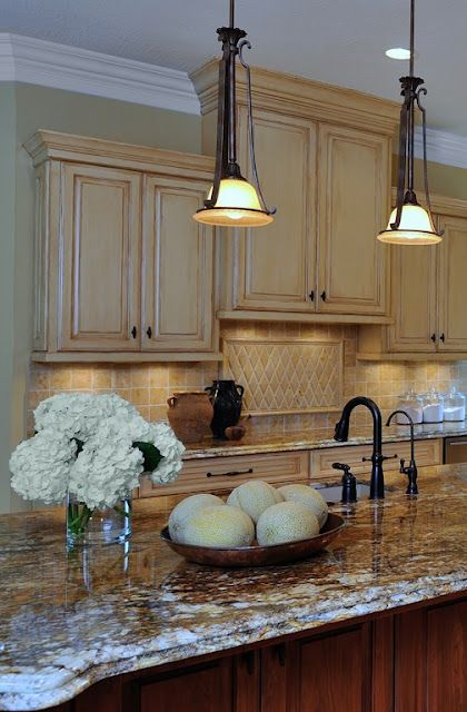 Kitchen...like the rubbed/antiqued finish on the cabinets as well as the raised cabinet with the decorative tiled area below it.