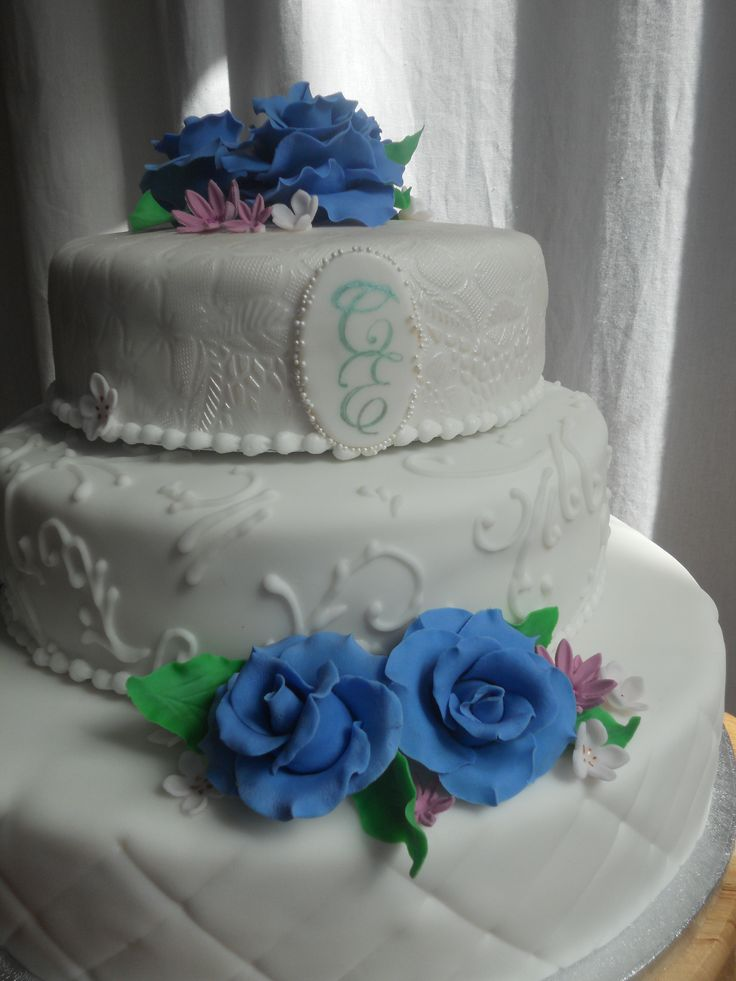 Basic 3 style wedding cake with handpainted initials en purple/blue roses. Curls on second tier are inspired by the invitations. www.taart-deco.nl