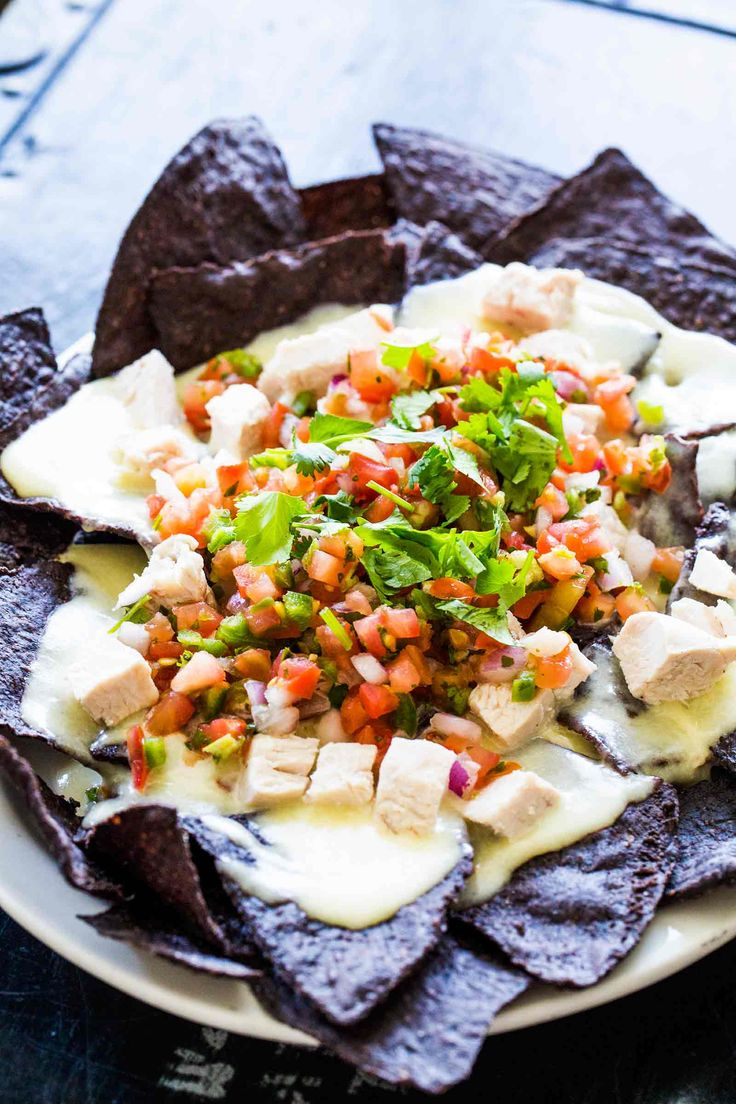 Celebrate the Red, White and Blue with these Blue Corn Tortilla Chip Nachos! With a creamy pepper jack cheese sauce, chicken, and pico de gallo. On SimplyRecipes.com
