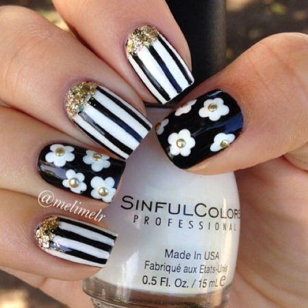 unhas decoradas floral e listrado em preto e branco e detalhes dourados