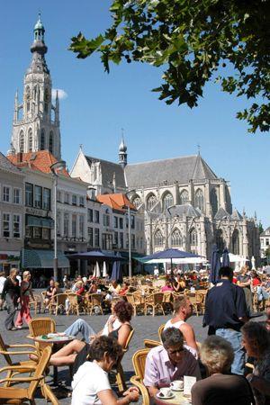 Terrassen op de Grote Markt, Breda, Nederland. Op de achtergrond de Onze Lieve Vrouwe kerk. (15de eeuw).