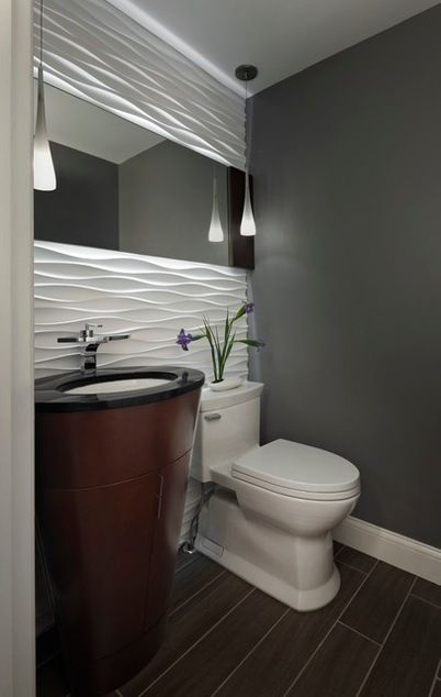 The wave like tiles and the glow of the backlit mirror.  Contemporary Powder Room by Xstyles Bath + More