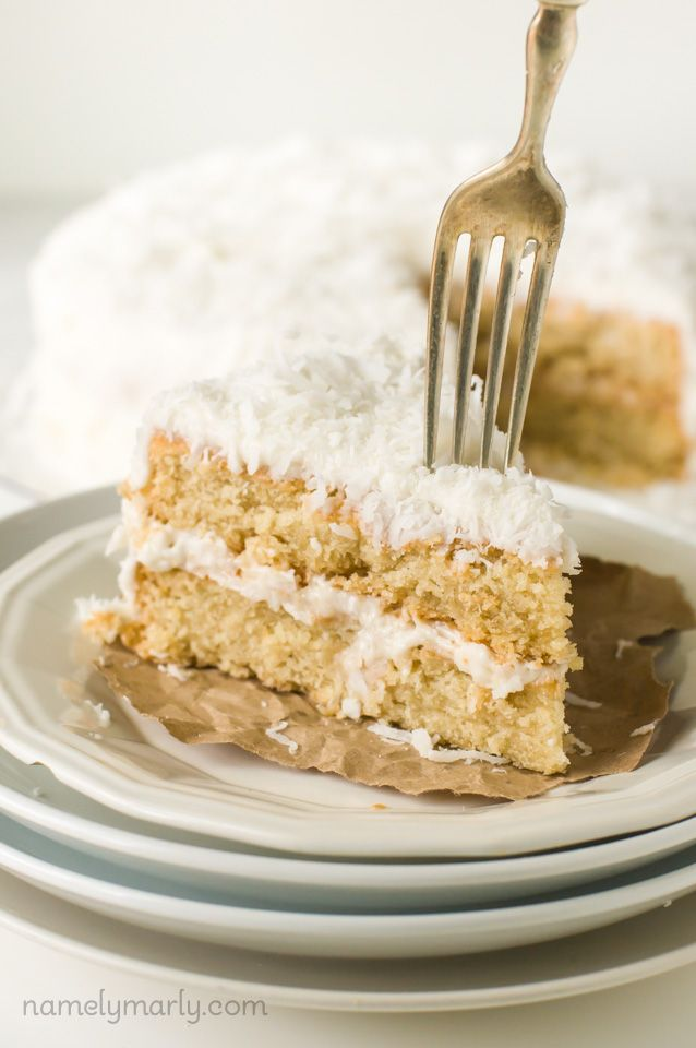 Vegan Coconut Cake with creamy filling and lots of coconut flakes on top!