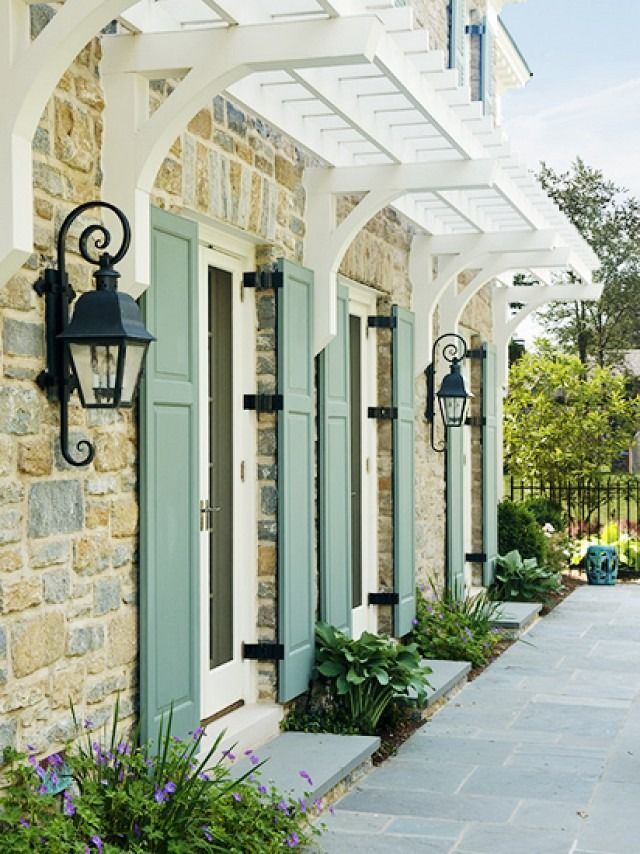 Such a charming stone facade with sage green shutters and iron lanterns!