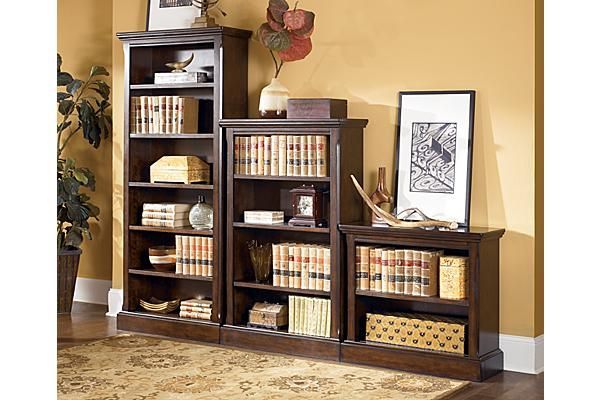 """The Porter Large Bookcase from Ashley Furniture HomeStore (AFHS.com). The warm rustic beauty of the """"Porter"""" home office collection uses a deep burnished brown finish flowing beautifully over the decorative framed details and stylishly turned bun feet perfectly complemented by the dark bronze color hardware to create an inviting furniture collection that fits comfortably into any home office decor."""