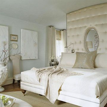 """Boudoir Glamour  In the master suite, a tufted mini wall covered in ivory satin extends the upholstered luxury of the king-size bed all the way to the ceiling. The creamy color scheme gives the room maximum Hollywood glamour.  Several large windows illuminate the room. """"I don't think you can have too much natural light in a house,"""" architect Harrison says."""