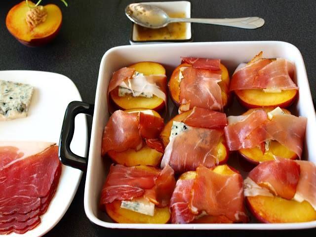 Brzoskwinie zapiekane z serem pleśniowym  9 wąskich plastrów szynki parmeńskiej ser pleśniowy zielony, 9 połówek brzoskwiń, 2 łyżki dżemu agrestowego.  Brzoskwinie umyć przekroić na pół i usunąć pestki. Ser pokroić w kostkę. Nałożyć odrobinę dżemu (1/4 łyżeczki) w miejsce po pestce w brzoskwini. Na dżemie ułożyć kawałek sera. Całą połówkę brzoskwini zawinąć w plaster szybki. Brzoskwinie ułożyć w naczyniu żaroodpornym i piec w piekarniku nagrzanym do 180stC z termoobiegiem przez ok 10 minut.