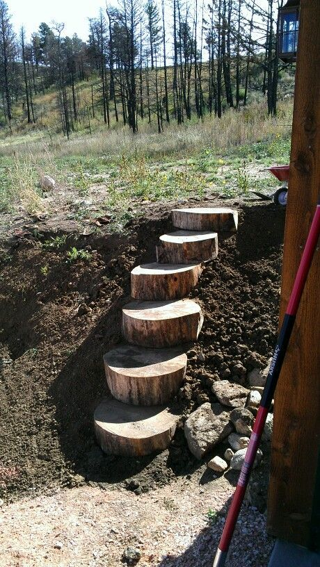 Log stairs on the side of the garage. Build in a slope next to stairs and you have an easy bike push path.: