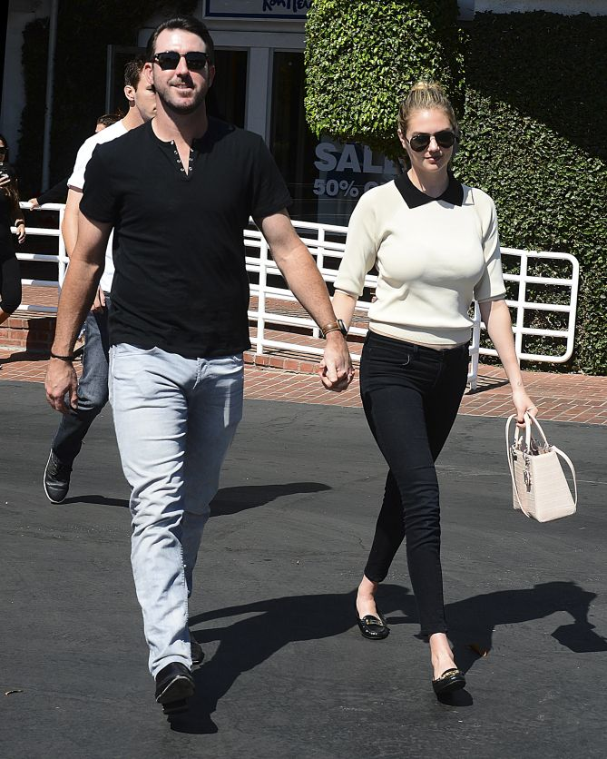 Kate Upton & Justin Verlander hold hands while donning classic aviator and wayfarer shades.