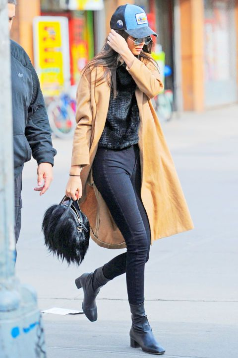 Stepping out in New York City, the model kept covered in a camel coat, black skinny jeans and Sandro boots. She gave her look an early-aughts edge by accessorizing with a trucker hat.
