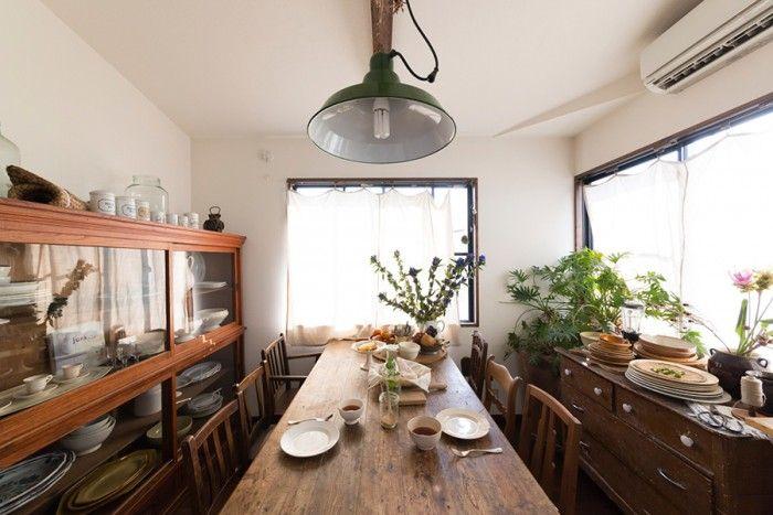 フランスのアンティークのテーブルに、日本の水屋箪笥、無骨なペンダントライトが不思議な統一感を生む。窓際には花やグリーンを欠かさない。