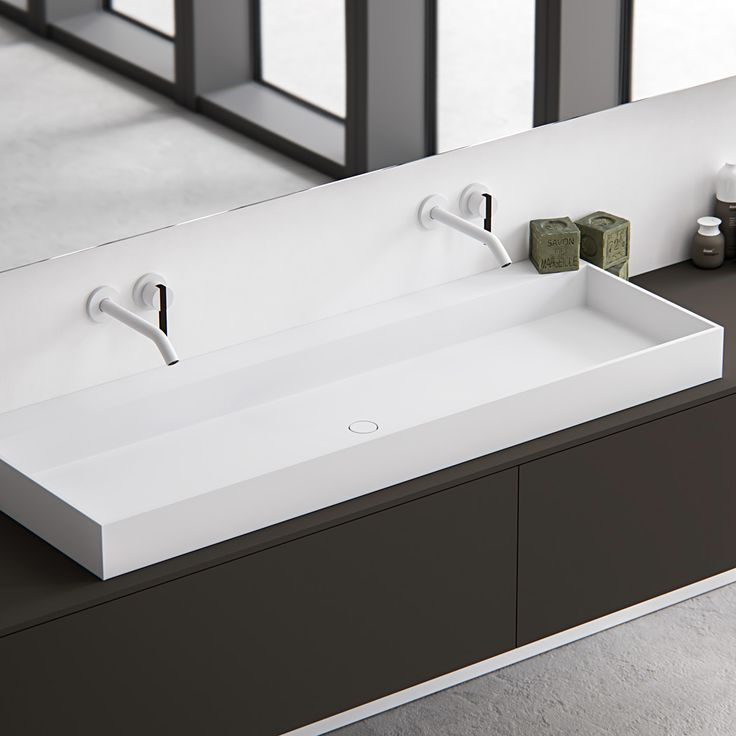 Edge, simple yet sophisticated and characterised by its minimalist rectangular appearance and thin 12mm edge. A completely (hand) made to measure basin out of HI-MACS (solid surface). This basic-shaped basin is ideal for design purposes and easily adaptable. Featured: Edge top mounted washbasin in Alpine white HI-MACS on top of a Fenix NTM wall mounted cabinet.