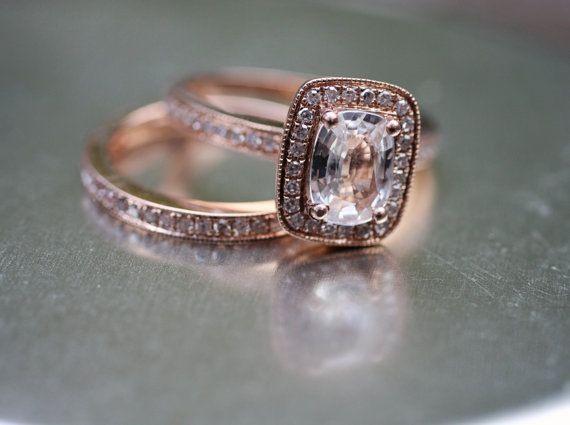 Wedding set. Engagement ring is a 1.2CT cushion cut white sapphire set in 14K rose gold with approx 0.25CT pave diamond halo. Wedding band is matching rose gold with approx 0.15CT eternity diamonds and milgrain edges.