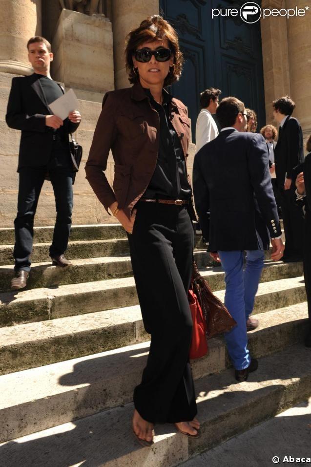 Inès de la Fressange in a brown blazer, black shirt and pants, brown leather belt, and sandals.