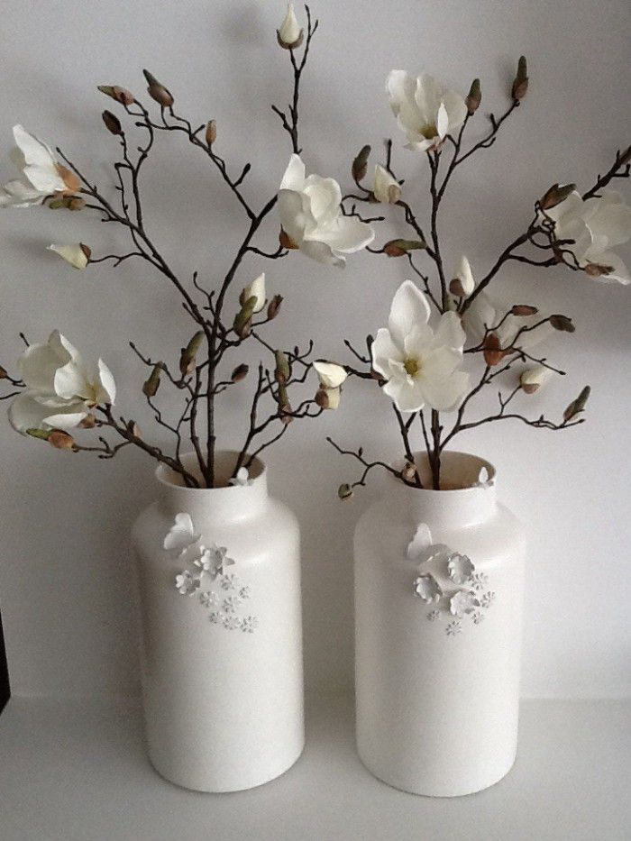 Two glass vases purchased (action) with matt white painted white. When using cupcake decoration plugs birdies flowers and butterflies out of clay. These pasted on it and again painted.