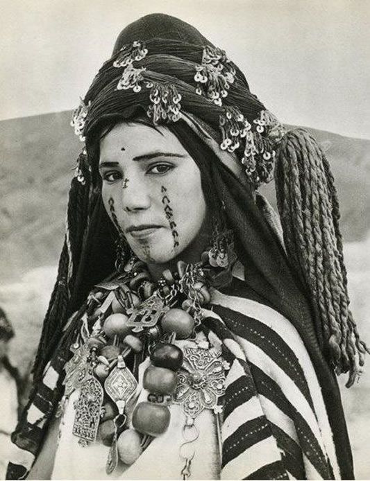 """Traditional facial tattoos run down the cheeks and chin of this Berber woman, photo ~ early 1950's."""