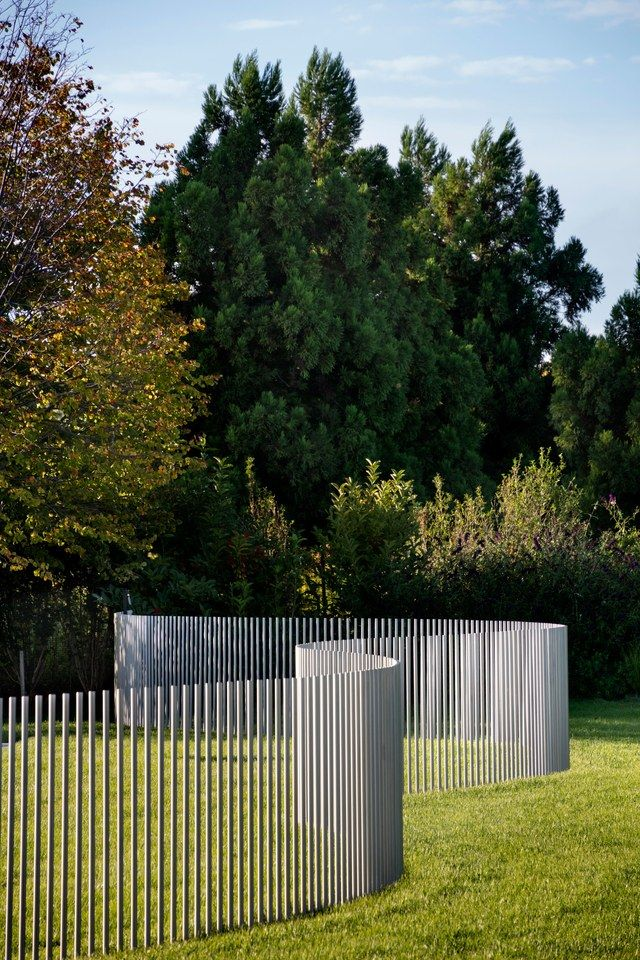Bohlin designed the fence to complement the architecture. Made only of stainless-steel posts in a serpentine arrangement, it reads more like a sculpture than a barrier (but it meets legal requirements for enclosing the pool) | archdigest.com