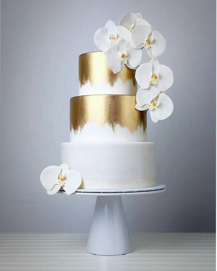 Gold and white wedding cake with white orchids