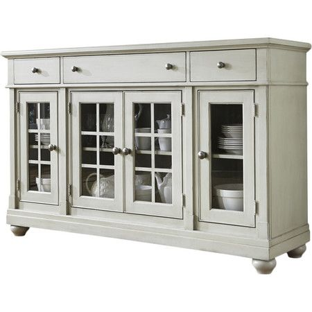 Stow crisp white dinnerware and gleaming glassware in eye-catching style with this stylish sideboard, showcasing 3 drawers and glass-paneled fronts.