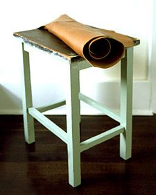Revitalize a scruffy tabletop by adding a leather surface. Putty and sand any ridges or bumps in the table; the leather should hide pits and scratches.