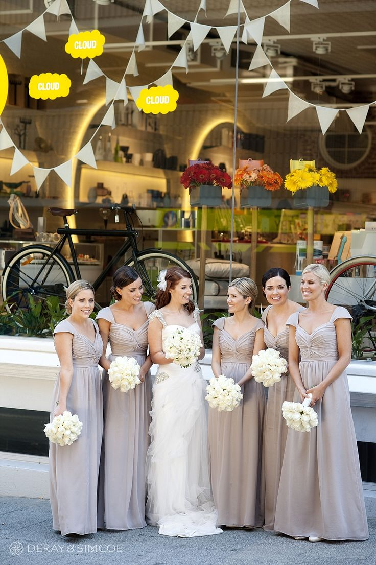Bride and Bridesmaids out the front of the Ven art gallery. Bridesmaids dressed in floor length dusk dresses with white rose bouquets. Flag window display Location ~ King Street, Perth  Photography by DeRay & Simcoe