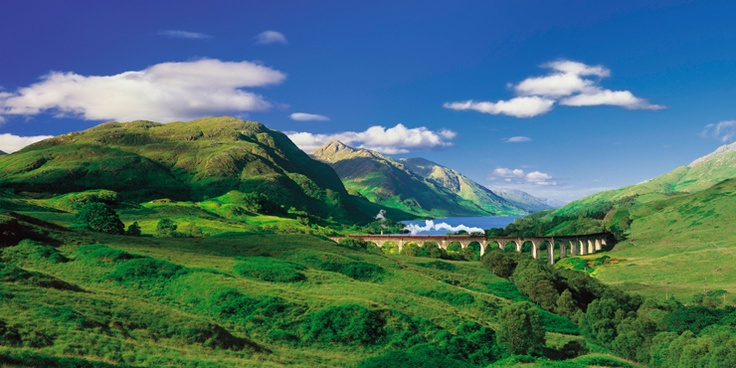 A steam train passes over the Glenfinnan Viaduct with views to Loch Shiel beyond