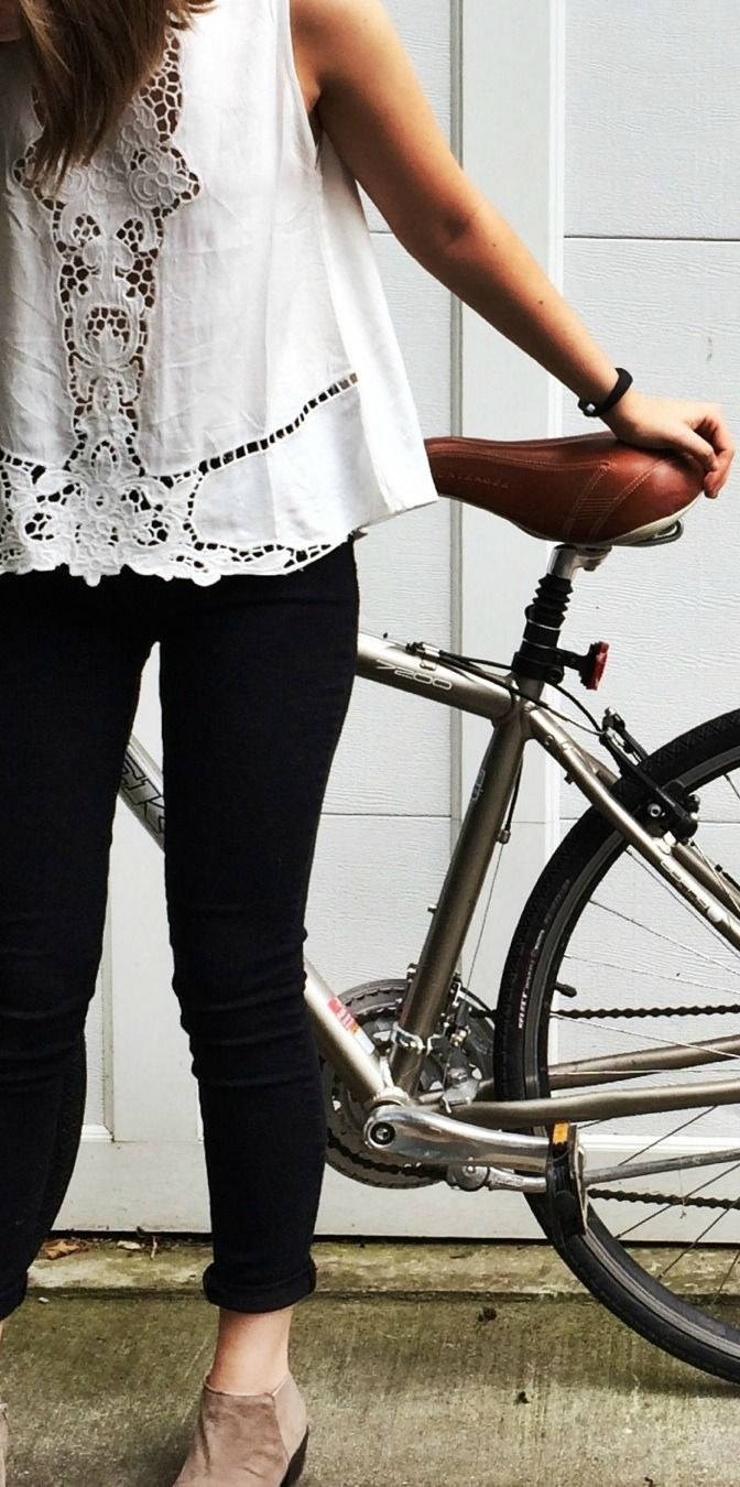 White blouse, black trousers and brown short boots. Biker look. Fashion trend. Romantic style. Vintage inspiration.