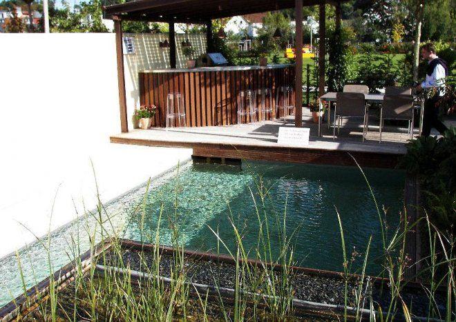 Schwimmteich mit Terrasse und Gartenküche.