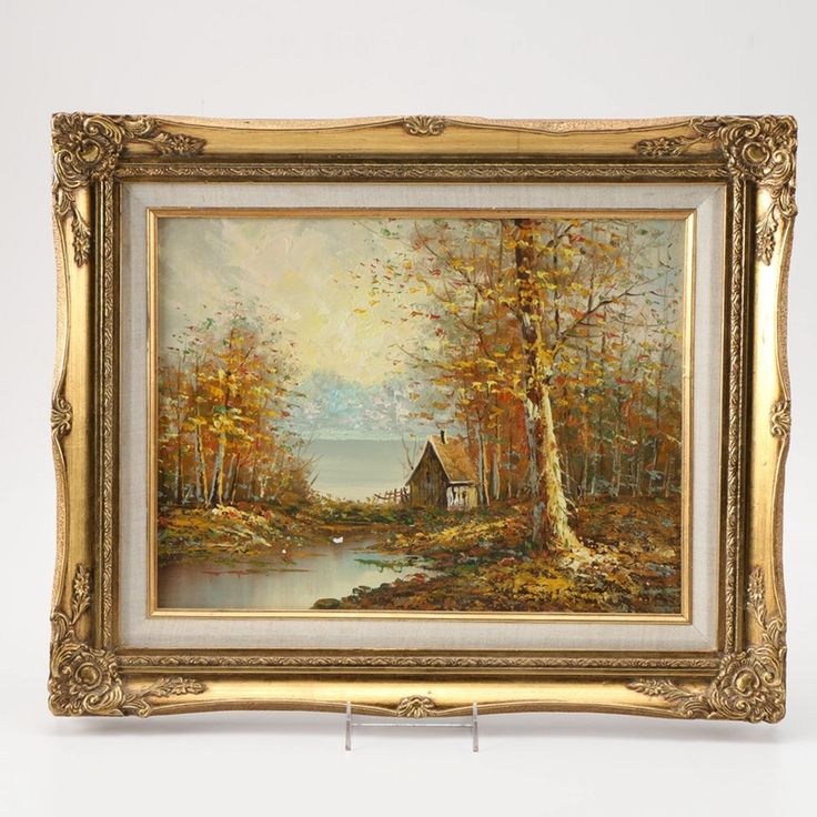 An oil painting on canvas of a landscape. This Impressionist style painting depicts a lone wooden shack situated near a quiet stream populated with various trees containing stippled leaves in a palette of ochre, yellow, green and red. An illegible artist signature is found to the lower right corner of the composition. The painting is presented in a gold tone wooden frame featuring moulded patterning and a linen inlay liner with hanging wire to the verso.
