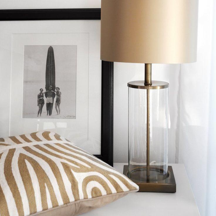 www.longcoastliving.se Longcoast Living Lampfot i glas och mässing. Guldig lampskärm och beige, zebramönstrad kudde.