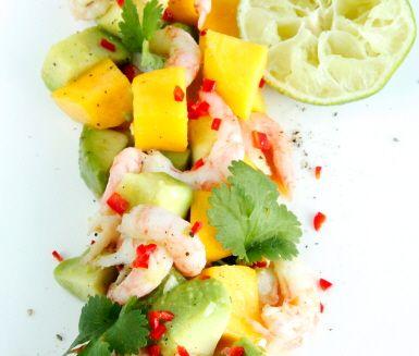 Ljuvlig ceviche med söt mango, krämig avokado, het chilipeppar och färska räkor. Blanda alla ingredienser och pressa limesaft över. Garnera med aromatiska korianderblad och servera som en frisk förrätt.