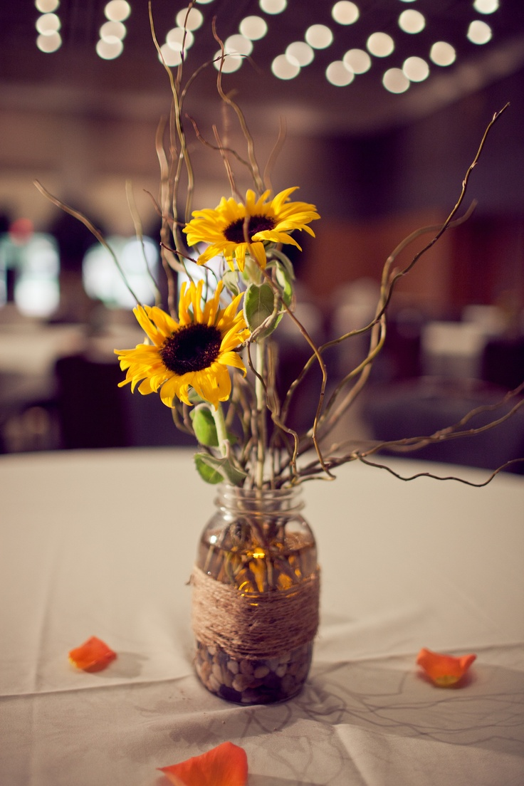 Centerpiece in mason jar with sunflower, river rock and curly branches
