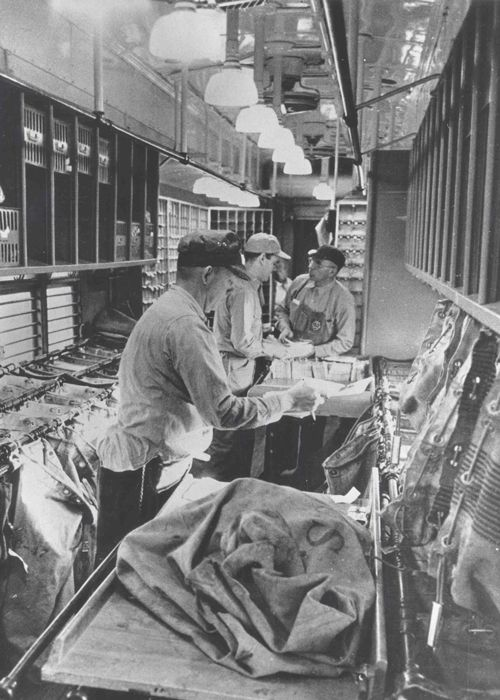 "Clerks sort mail in the cramped interior of a Railway Post Office (RPO). RPO interiors typically ranged from 15 to 60 feet long and were about 9 feet wide. Tight-knit crews of up to 20 men worked in the larger cars, racing the clock to sort mail in time for dispatch to the stations en route. ""Working the mail"" consisted of sorting letters into ""pigeon hole"" distribution cases and tossing mail accurately into labeled pouches, correctly routed to as many as 5,000 destinations."
