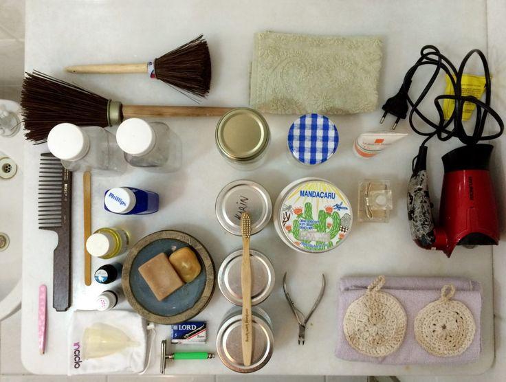 Banheiro desperdício zero: Da esquerda para direita: 1 escova de vaso, 1 escova de limpeza geral, 5 mini toalhas, 1 pente, 1 lixa de unha, 2 garrafinhas, enxágüe bucal, fio dental, 1 filtro solar (esqueci na foto anterior), 1 secador de cabelo, leite de magnésio, 3 óleos essenciais, 1 porta sabonete, pasta de dente, demaquilante, esfoliante, 1 creme corporal e 1 facial, 1 perfume, 1 pinça, 1 coletor menstrual, 1 barbeador e láminas, 1 escova de dente, 1 cortador de unhas, mais toalhinhas e 2…