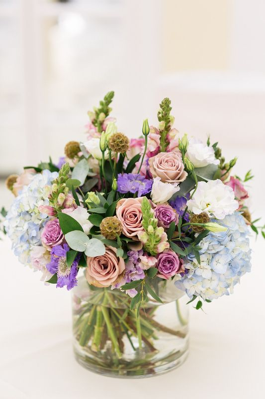 Low glass cylinder vases filled with a hand tied arrangement of purple and blue flowers for the ceremony table, at Blenheim Palace