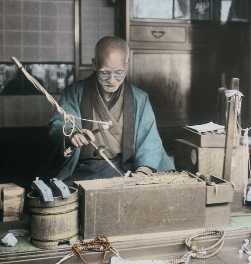 Hand-colored photo of a craftsman making Buddhist prayer beads. Early 20th century (1900-1920), Japan. Photographer unknown