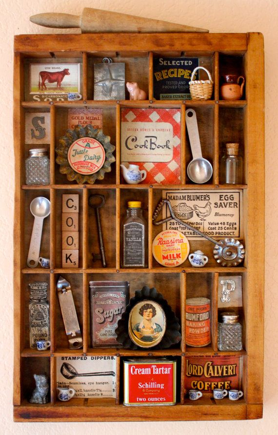 This is a Kitchen Assemblage made of found objects and vintage illustrations. The assemblage is contained in a vintage wooden drawer or type tray