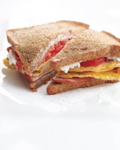Satisface tu antojo de sándwich en el desayuno con: claras de huevo, queso de cabra, tocino canadiense y pan integral. La receta aquí.