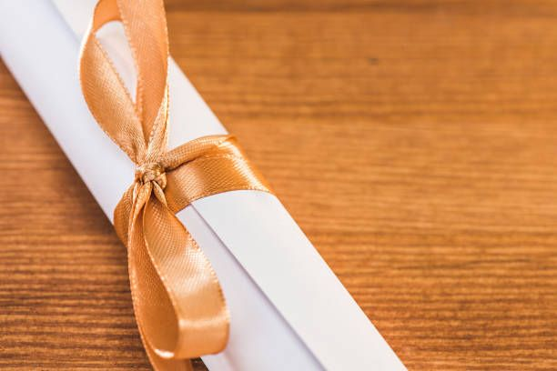 close up view of graduation university diploma with ribbon on wooden